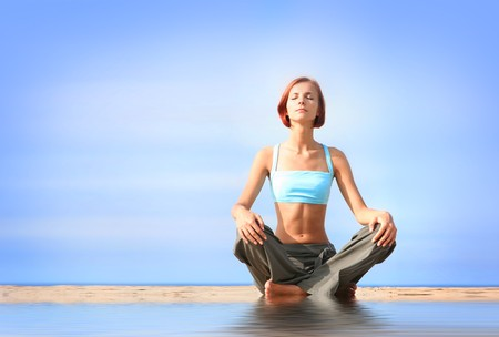 young girl meditating on the beach  Stock Photo