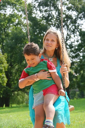 beautiful young mother with cute kid on swing photo