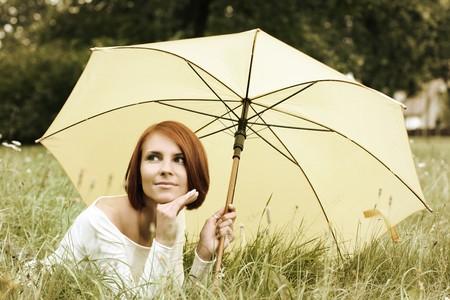 beautiful girl relaxing on grass under yellow umbrella photo