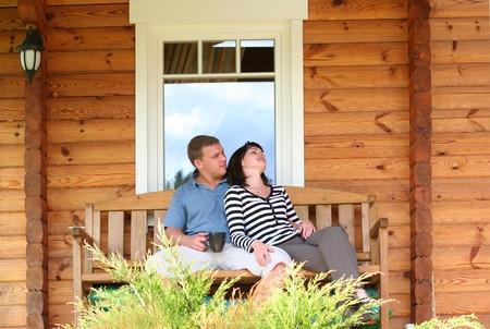 young couple drinking tea on verandah photo