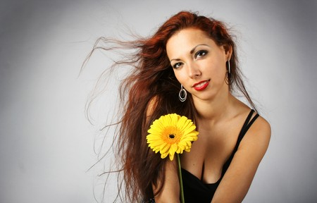 beautiful lang-haired girl with yellow flower photo