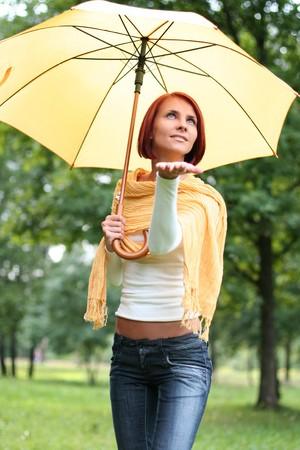 beautiful young girl under yellow umbrella photo