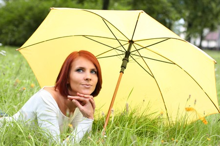 beautiful girl relaxing on grass under yellow umbrella photo