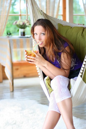 beautyful long-haired girl drinking lemonade in comfortable cottage photo