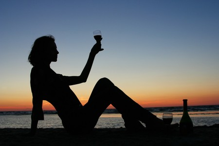 young girl drinking wine on the beach