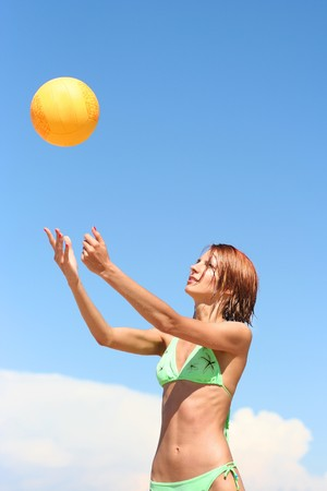 young girl playing volley-ball on the beach photo