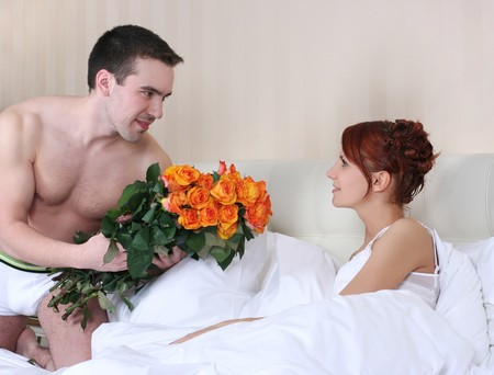 young man bringing flowers in bed