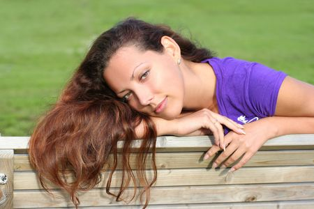 beautiful long-haired girl relaxing in park photo