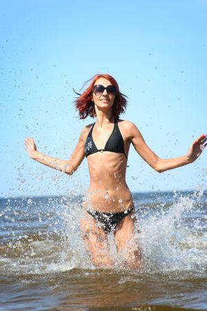 beautifil girl running in the sea photo