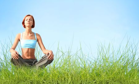 beautiful young woman meditating outdoors