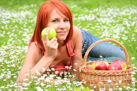 beautiful girl with a basket of apples on a meadow photo