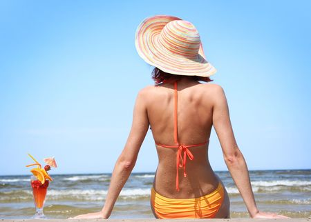 young woman with fruit cocktail relaxing on beach