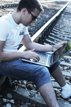 attractive young guy with laptop on rails Foto de archivo