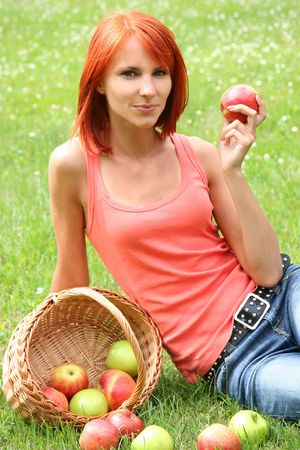 beautiful girl with a basket of apples on a meadow
