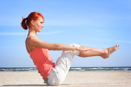 young woman working out on the beach