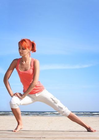 young woman working out on the beach photo