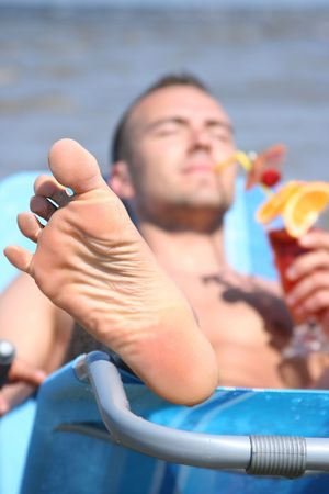young guy relaxing with cocktail (focuc on foot) photo