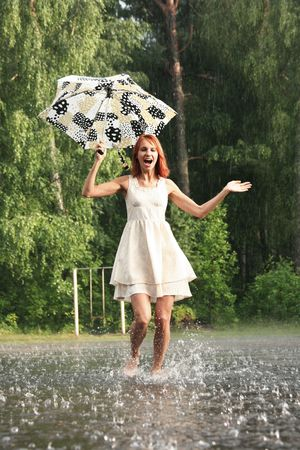 happy young woman running under rain Stock Photo
