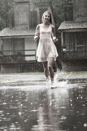 rain wet: attractive young girl running in the rain