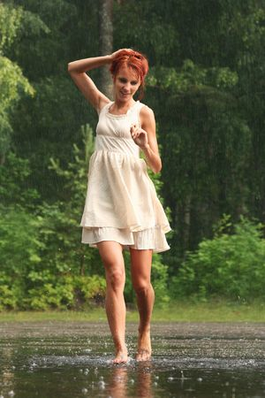happy young woman in the rain without an umbrella photo