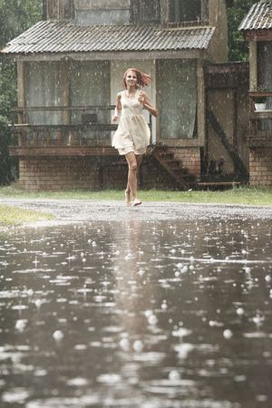 autumn rain: young woman running in the rain without umbrella Stock Photo