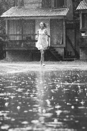 walking in the rain: young woman running in the rain without umbrella Stock Photo