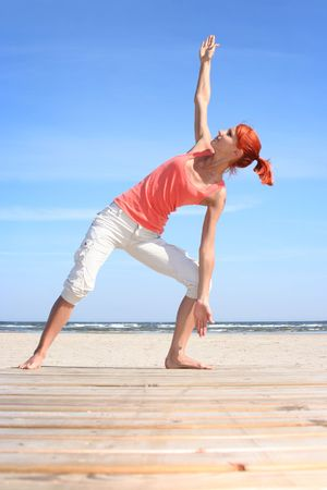 beautiful young girl stretching at the beach photo