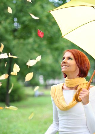 beautiful young girl under yellow umbrella in the autumn park photo