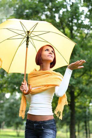 beautiful young girl under yellow umbrella Stock Photo