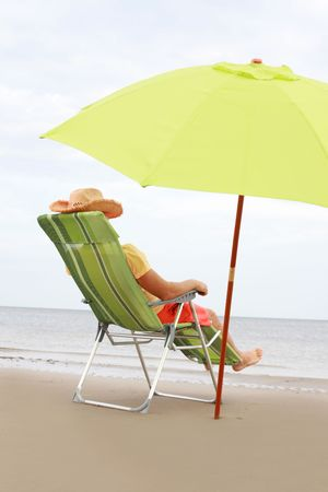 young guy in green chair  on the beach  photo