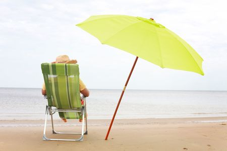 young guy in green chair  on the beach  Stock Photo