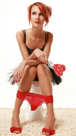 funny girl with red lollipop in the toilet Stock Photo - 5558407