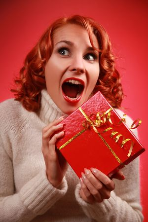 joy of giving: funny redhead woman with bright red present