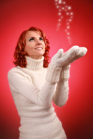 pretty young woman with snow flakes on red background photo