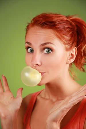 funny redhead girl with bubble gum on green background photo