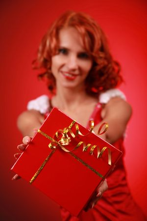 beautiful young Santa-girl with present (present in focus) photo