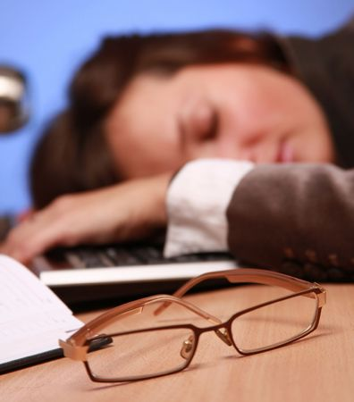 young businesswoman fell asleep at work (glasses in focus ) photo