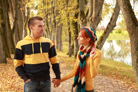 beautiful young couple walking in autumn park photo