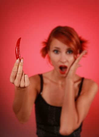 beautiful woman with red hot pepper (hand on focus) photo