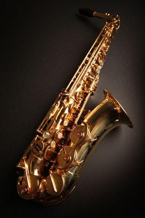 golden shiny saxophone on black background photo