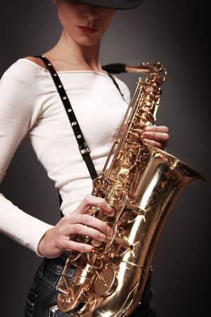 sexy young woman with saxophone (sax in focus) photo