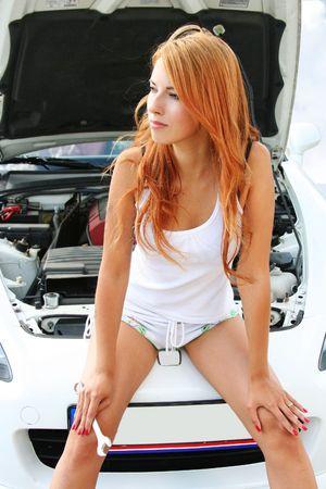 beautiful redhead girl repairing a car