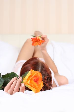 young woman in bed with orange rose (hand in focus) Stock Photo - 5933562