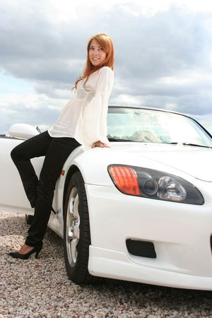 beautiful young woman with white luxury car photo