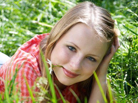 Portrait of beautiful woman lying at grass photo