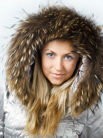 straight jacket: Beautiful blonde girl in fur hood looking straight and smiling