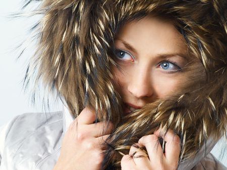 comely: Young women wearing a winter jacket with her hood up and over her head.
