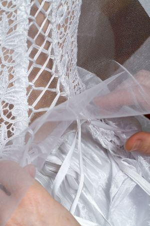 zip tie: Bride getting her white wedding dress tied at the back