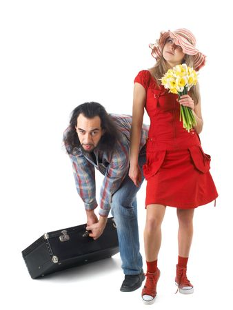 careless: a couple at journey, man pulling heavy luggage and careless woman standing near isolated on white