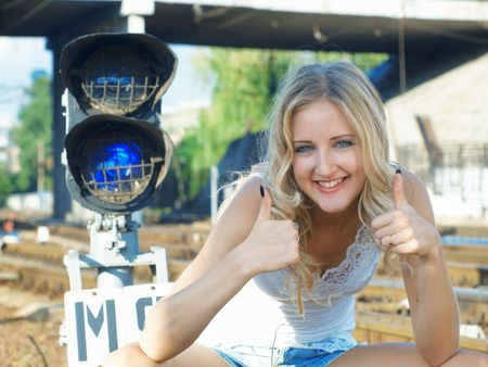 Smiling blonde girl sitting on a railway track photo